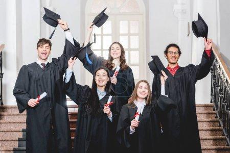 Photo pour Heureux groupe d'étudiants souriant tout en tenant des casquettes de graduation - image libre de droit