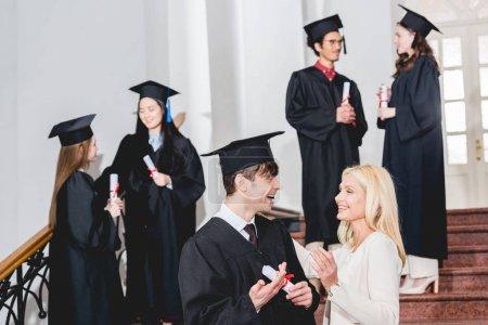 Foto de Selective focus of happy son in graduation cap looking at mother near students - Imagen libre de derechos
