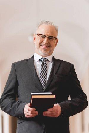 Photo pour Joyeux mature enseignant dans des lunettes tenant des livres et regardant la caméra - image libre de droit