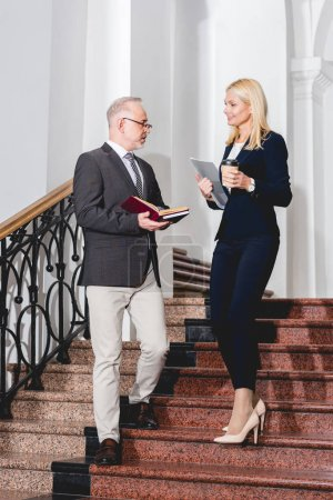 Photo for Teacher in glasses holding books and looking at blonde colleague with paper cup standing on stairs - Royalty Free Image