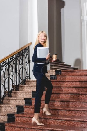 Photo for Happy and attractive blonde teacher holding folder and disposable cup - Royalty Free Image