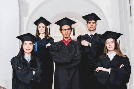 Photo pour Étudiants joyeux dans des robes de graduation restant avec les bras croisés dans l'université - image libre de droit