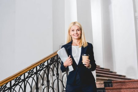 Photo for Cheerful and attractive blonde teacher holding folder and disposable cup - Royalty Free Image