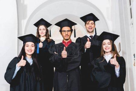Photo pour Étudiants gais dans des robes de graduation restant et affichant des pouces vers le haut - image libre de droit