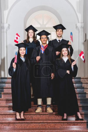 Foto de Cheerful students in graduation gowns holding flags of different countries - Imagen libre de derechos