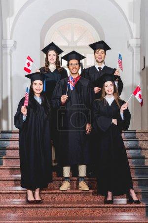 Photo pour Étudiants gais dans des robes de graduation retenant des drapeaux de différents pays - image libre de droit