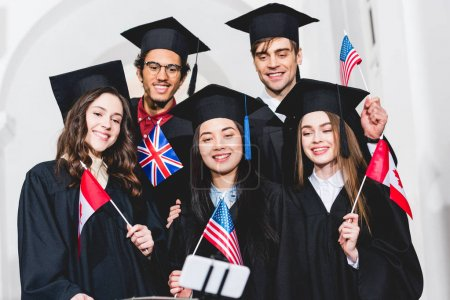 Photo pour Selective focus of cheerful students in graduation gowns holding flags of different countries and taking selfie on smartphone - image libre de droit