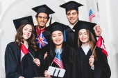 selective focus of cheerful students in graduation gowns holding flags of different countries and taking selfie on smartphone