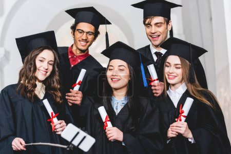Photo pour Cheerful group of students in graduation gowns holding diplomas while talking selfie - image libre de droit