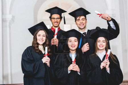 Photo for Happy group of students in graduation gowns smiling and holding diplomas - Royalty Free Image