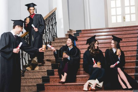 Photo pour Cheerful group of students in graduation gowns sitting on stairs with paper cups and diplomas - image libre de droit