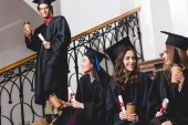 cheerful and attractive students holding paper cups and diplomas near student
