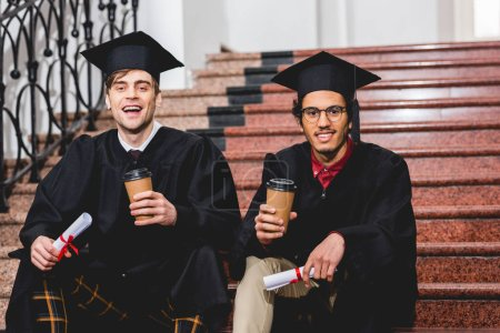Photo for Cheerful students in graduation caps holding diplomas and paper cups - Royalty Free Image