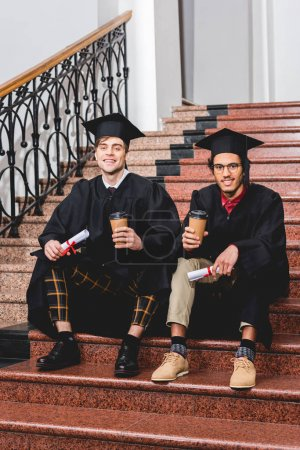 Photo pour Cheerful students in graduation gowns holding diplomas and paper cups while sitting on stairs - image libre de droit