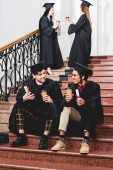 selective focus of cheerful students in graduation gowns holding diplomas and paper cups while sitting on stairs