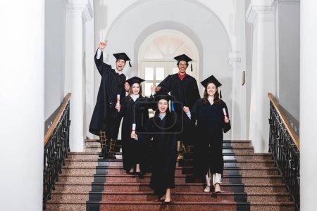 Photo pour Groupe gai d'étudiants dans des robes de graduation faisant des gestes tout en détenant des diplômes - image libre de droit