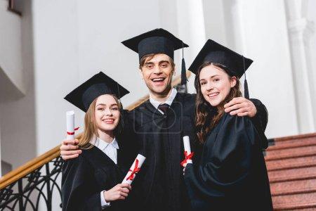 Photo pour Homme gai dans le chapeau de graduation étreignant les filles attrayantes tout en tenant le diplôme - image libre de droit