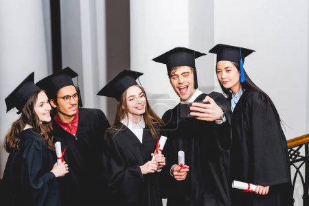 Photo pour Cheerful students in graduation gowns taking selfie and smiling while holding diplomas - image libre de droit