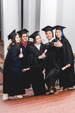 Photo pour Happy students in graduation gowns taking selfie and smiling while holding diplomas - image libre de droit