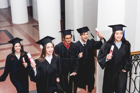 Photo for Smiling students in graduation gowns holding diplomas in university - Royalty Free Image