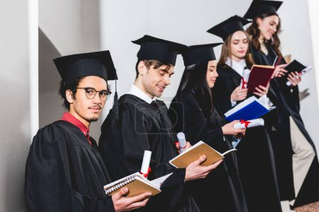Photo pour Low angle view of man in glasses looking at camera near students in graduation caps reading books - image libre de droit