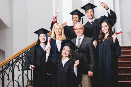 Photo pour Cheerful students in graduation caps holding diplomas near happy teachers - image libre de droit