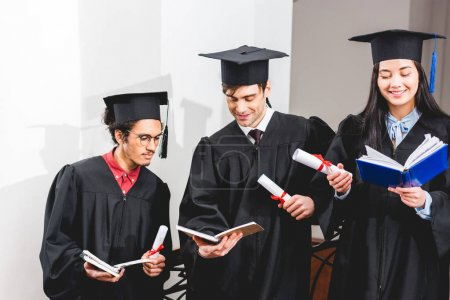 Photo for Happy girl reading book near students in graduation caps holding diplomas - Royalty Free Image