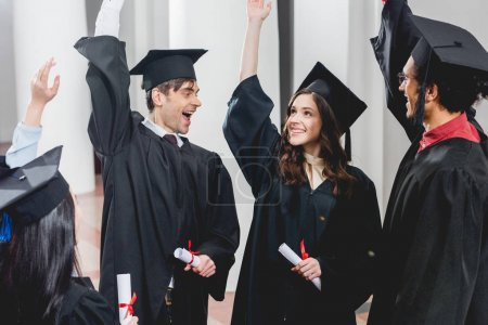 Photo for Smiling group on students in graduation gowns holding diplomas and putting hands above head - Royalty Free Image