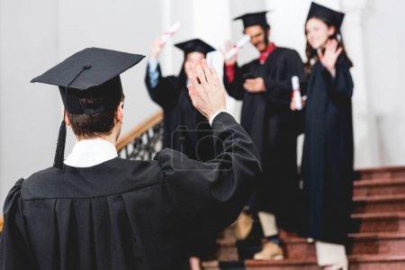 Photo pour Foyer sélectif de l'étudiant dans la main d'ondulation de chapeau de graduation - image libre de droit