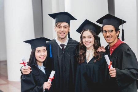 Photo for Smiling group on students looking at camera while holding diplomas - Royalty Free Image