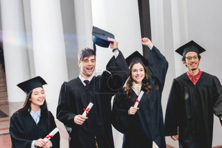 Photo for Happy group on students gesturing and celebrating graduation while holding diplomas - Royalty Free Image