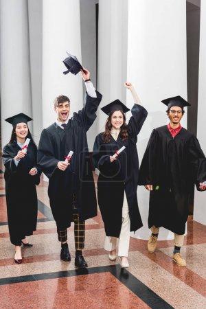 Photo pour Groupe joyeux sur les étudiants gesticuler et célébrer l'obtention du diplôme tout en tenant des diplômes - image libre de droit