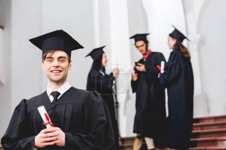 Photo pour Foyer sélectif de l'homme heureux en robe de remise des diplômes regardant la caméra et détenant un diplôme près des étudiants - image libre de droit