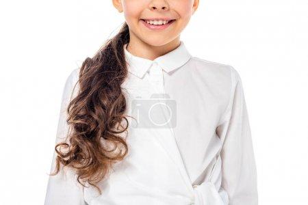 Photo pour Vue recadrée de l'écolière en tenue formelle souriant isolé sur blanc - image libre de droit