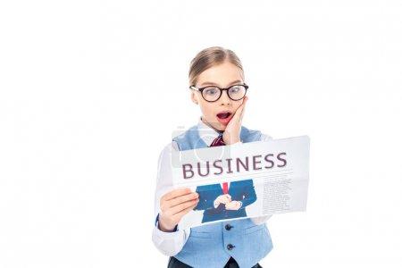 Photo pour Surpris écolière en tenue formelle geste et lecture journal d'affaires isolé sur blanc - image libre de droit