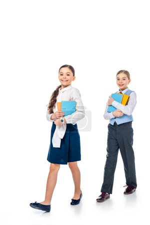 Photo for Schoolgirls in formal wear holding books and looking at camera On White - Royalty Free Image