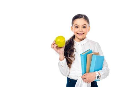 Photo pour Écolière de sourire retenant la pomme et les livres tout en regardant l'appareil-photo d'isolement sur le blanc avec l'espace de copie - image libre de droit