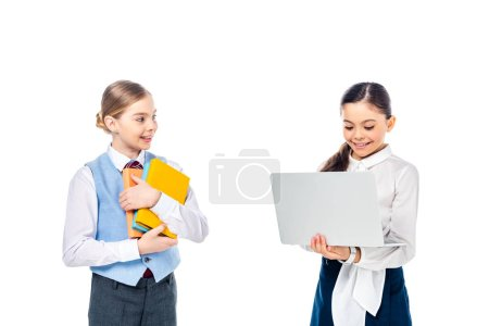 Photo for Smiling schoolchildren in formal wear using laptop and holding books Isolated On White - Royalty Free Image