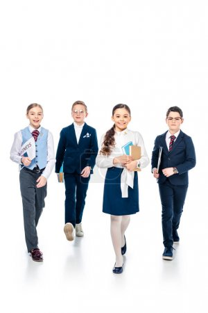 Foto de Escolares fingiendo ser empresarios con libros y periódicos caminando sobre blanco - Imagen libre de derechos