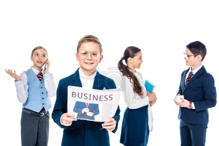 Foto de Smiling schoolboy with newspaper near schoolchildren pretending to be businesspeople Isolated On White - Imagen libre de derechos