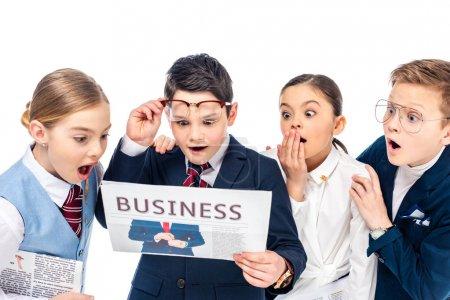 Foto de Escolares sorprendidos fingiendo ser empresarios leyendo el periódico Isolated On White - Imagen libre de derechos