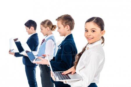 Photo pour Écoliers en tenue formelle prétendant être des gens d'affaires en utilisant des ordinateurs portables isolés sur le blanc - image libre de droit