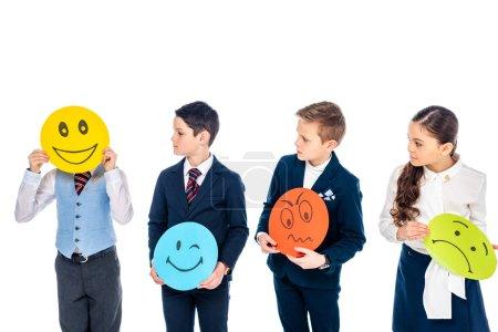 Photo pour Écoliers tenant des cartes avec diverses expressions du visage et regardant enfant couvrant visage avec carte isolé sur blanc - image libre de droit