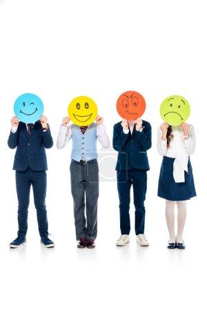 Photo pour Écoliers en tenue formelle couvrant les visages avec des cartes aux expressions faciales variées Sur Blanc - image libre de droit