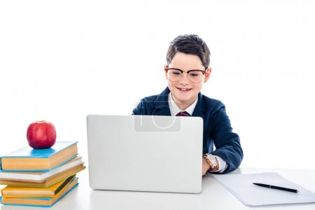 Photo for Schoolboy in glasses sitting at desk with books and using laptop isolated on white - Royalty Free Image