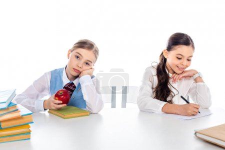 Photo for Schoolgirls in formal wear sitting at desk with books and writing Isolated On White - Royalty Free Image
