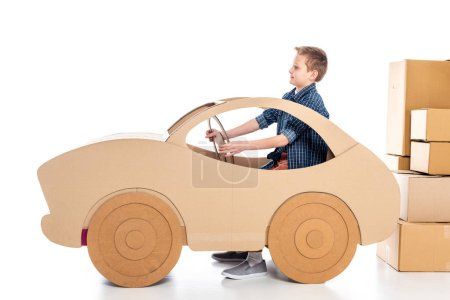 Photo for Boy sitting in cardboard car and holding steering wheel on white - Royalty Free Image