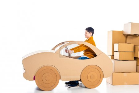 Photo for Boy sitting and playing with cardboard car near packages on white with copy space - Royalty Free Image