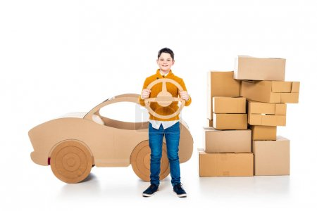 boy near cardboard car holding steering wheel and looking at camera on white