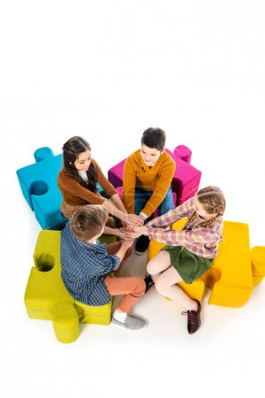 Foto de High Angle View of kids sitting on jigsaw puzzle poufs and Stacking Hands Isolated On White - Imagen libre de derechos